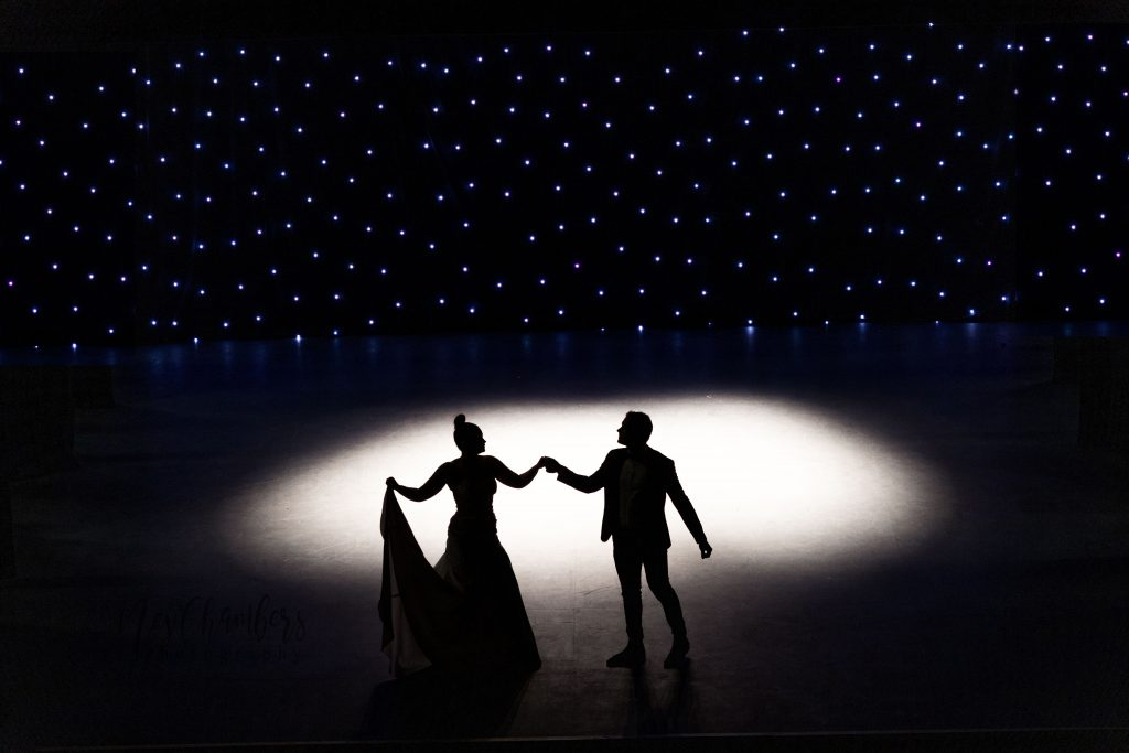 Bride and groom dancing just out of spotlight. Stars in background.
