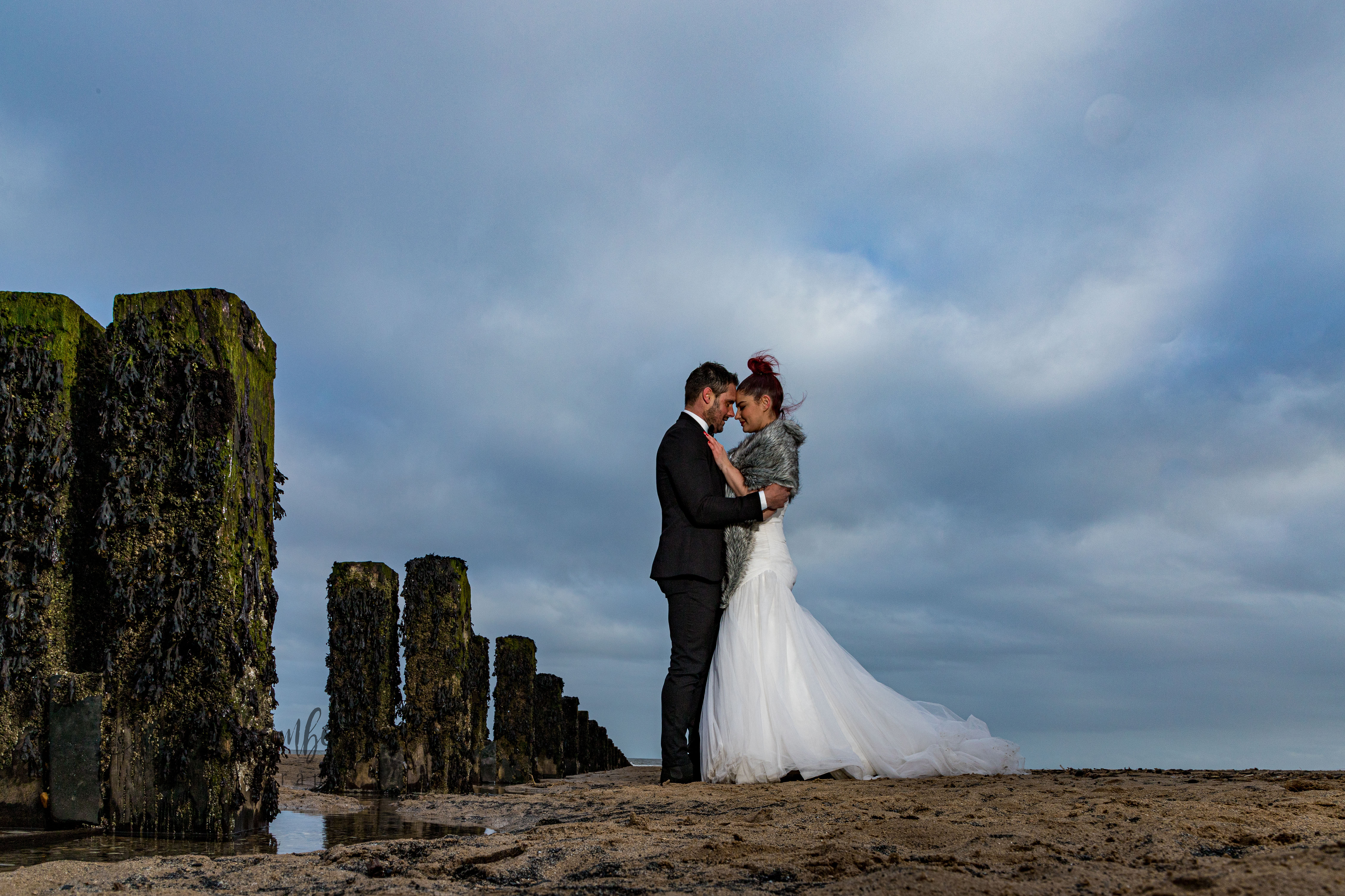 Bride and Groom embrace on beach. Blue sky with fluffy clouds.